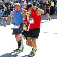 photo of two men helping injured runner, Boston Marathon
